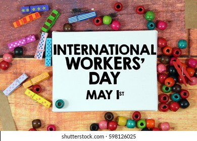 A happiness concept image of a colorful beads and cute clothespin scattered over a colorful wooden texture background with a white canvas and a word celebrate INTERNATIONAL WORKERS DAY - MAY 1