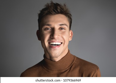 Happiness concept. Portrait of cheerful male person with snow white teeth and disheveled short hair. Isolated on background