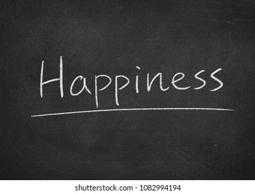 happiness concept word on a blackboard background