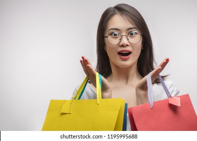 happiness, consumerism, sale and people concept - charming young Asian shopaholic girl with shopping bags and credit card over studio white background. Consumerism and Shopping Concept