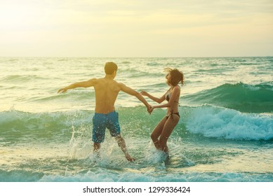 Happiness couple in romantic scene on the beach at sunset. Love and valentine concept.