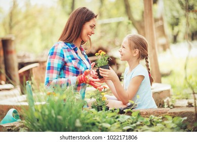 Happiness cute little girl assisting her smiling mother planting flowers in a backyard.