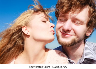 Happiness dating concept. Couple in love blonde woman handsome bearded man enjoy romantic date kissing, outdoor wide angle view