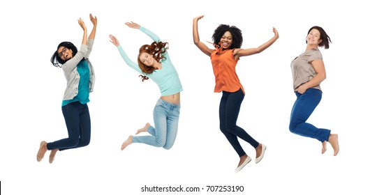 happiness, diverse, motion and people concept - happy international women jumping in air over white background