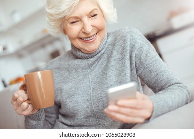 Happiness elderly woman watching video in phone and drinks coffee
