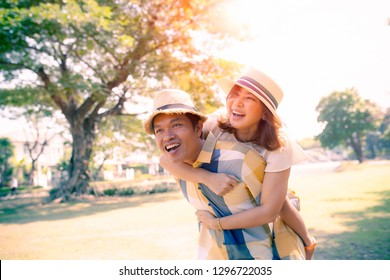 happiness emotion of asian man and woman toothy smiling face relaxing in public park
