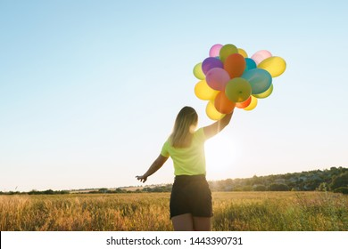 Happiness, enjoy the life, birthday party, bright moment, summer fun, creativeness. Young girl with big bunch of colorful balloons standing in sunset meadow