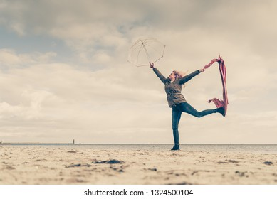 Happiness, enjoying weather, feeling great concept. Woman jumping with red scarf and transparent umbrella on beach near sea, sky with clouds in background