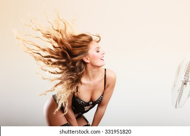 Happiness and freedom concept. Beauty happy sexy female model wearing lingerie underwear with wind in long curly hair. Indoor.