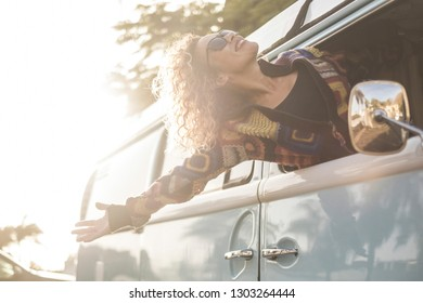 Happiness and freedom lifestyle concept with beautiful girl young caucasian female out of the vehicle enjoying the wind and feel the open air - travel and vacation transport concept for fashion girl