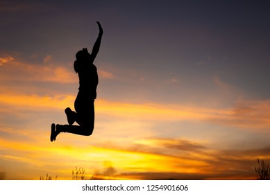 happiness, freedom, motion and people concept - smiling young woman jumping in air sunset background