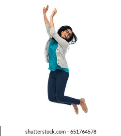 happiness, freedom, motion and people concept - smiling young indian woman jumping in air