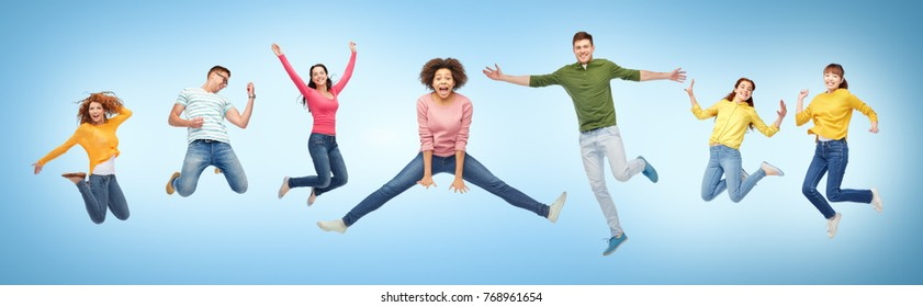 happiness, freedom, motion and people concept - smiling young international friends jumping in air over blue background