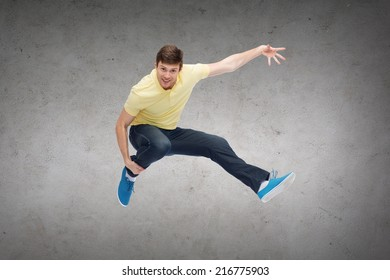 happiness, freedom, movement and people concept - smiling young man jumping in air over concrete wall background