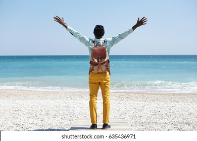 Happiness and freedom. People and travel. Unrecognizable dark skinned traveler with backpack raising outstretched arms while standing alone on broadwalk on beach, trying to embrace beauty around him