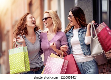 Happiness, friends, sale and fun concept-smiling young women with shopping bags.