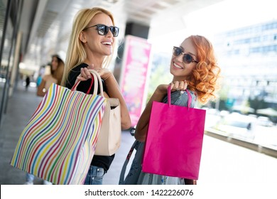 3caf987f8 Happiness, friends, shopping and fun concept-smiling young women with shopping  bags.