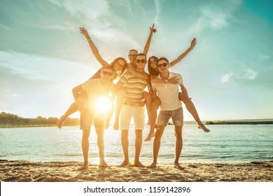 Happiness Friends stay in group on the beach under sunset sunlight in summer sunny day.