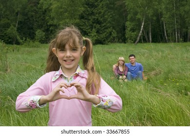Happiness girl shows heart. Mother and father are sitting on the grass in the park.  Young pretty girl make gesture heart.  Happy family.