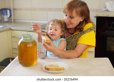 Happiness grandmother with the granddaughter eating honey with bread