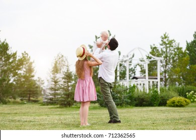 Happiness and harmony family life concept. Young mother and father with baby son in the park. Happy family resting together on the green grass at summer