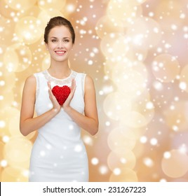 happiness, health, charity and love concept - smiling woman in white dress with red heart over beige background over beige lights background and snow