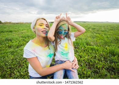 Happiness, Holi festival and holidays concept - Mother and her daughter covered with color powder smiling over nature background