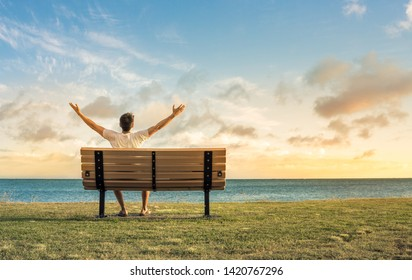 Happiness, hope and freedom concept- happy young man sitting on beach park bench feeling happy and free with arms up looking up to the sky.