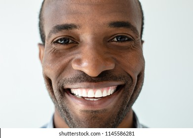 Happiness inside. Close up of joyful handsome adult afro american man smiling against white background