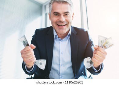 Happiness inside me. Delighted handsome man smiling and holding a lot of money