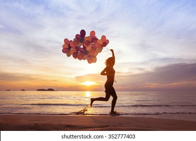 happiness and inspiration concept, psychology of happy people, young woman running with multicolored balloons on the beach