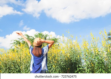 Happiness long hair woman in casual clothing with yellow flowers field
