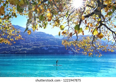 Happiness man standing on kayak boat at the blue lake and mountain background.Happy Vacation holiday in beautiful outdoor scene landscape. Travel Journey Freedom concept.