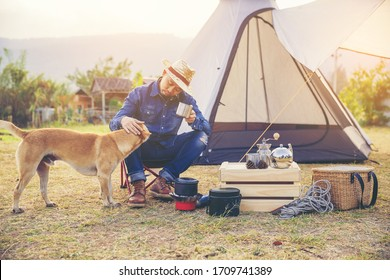 Happiness man traveling with dog on weekend enjoy with morning coffee and sunrise.