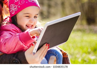 Happiness mom and daughter web surfing using tablet outdoors on a sunny day
