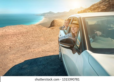 Happiness mother and son, sitting in white car and look on the beautiful ocean coastline with mountains. Travel, Family, Freedom concept.