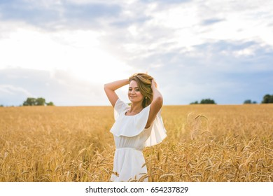 happiness, nature, summer, autumn, vacation and people concept - young woman in the field.