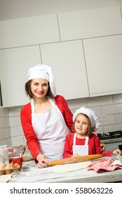 Happiness and people concept. Mother and daughter making dough in white kitchen. Happy family in making cookies at home. Happy kids cooking healthy meal in the white kitchen.