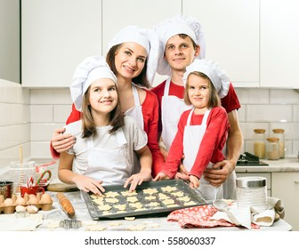 Happiness and people concept. Mother and father and  daughters making dough in white kitchen. Happy family in making cookies at home. Happy kids cooking healthy meal in the white kitchen.