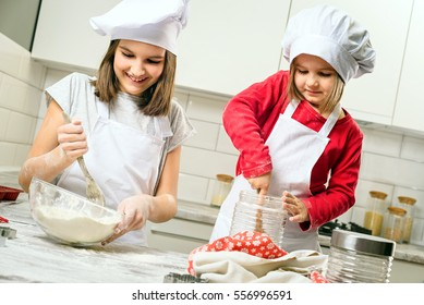 Happiness and people concept. Sisters making dough in white kitchen. Happy family in making cookies at home. Happy kids cooking healthy meal in the white kitchen.
