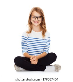 happiness and people concept - smiling girl in eyeglasses sitting on floor