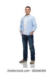 happiness and people concept - smiling man wearing shirt and jeans with hands in pockets
