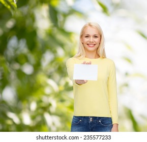 happiness and people concept - smiling young woman in casual clothes with white blank business or name card