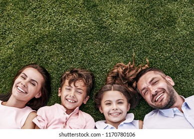 Happiness portrait. Family of four lying on grassy field smiling cheerful top view close-up