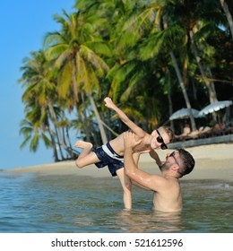 Happiness portrait in tropical water: bearded father throws his cute blond son above the water. Both in sunglasses, having fun on the empty beach