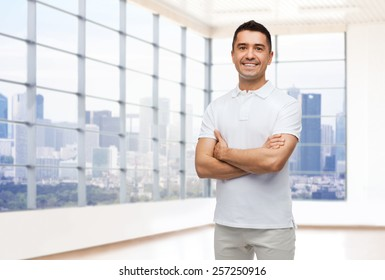 happiness, real estate and people concept - smiling man in white t-shirt over empty apartment or office room with big window and city view background