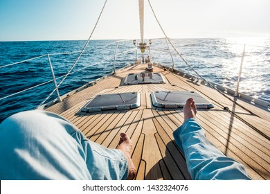 Happiness and relax concept for traveler people - man legs point of view on a wooden sail boat with sun and blue ocean around - luxury and holiday vacation outdoor leisure activity