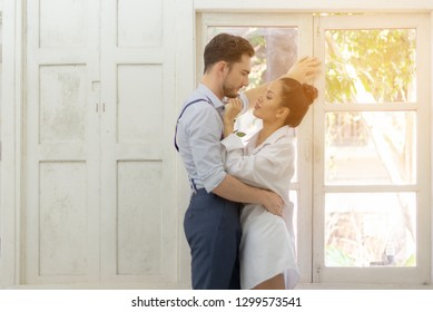 Happiness and romantic scene of love asian couples partners making eye contact in the white room
