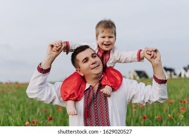 Happiness Smiling Child Son on Father Shoulders. Joyful Funny Characters Wearing Ukrainian National Cossack Garments. Red Flowers Poppy Field, Cloudy Sky and Village on Blurred Background