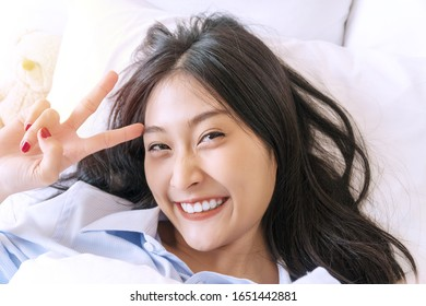 Happiness smiling young woman using smartphone for selfie on the bed for social media. Cheerful girl lying on white bed taking selfie photo using cell phone in morning at home. Lifestyle relax concept